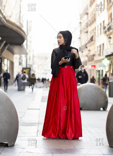 Portrait of young woman wearing black hijab standing on sidewalk with smart phone in hand