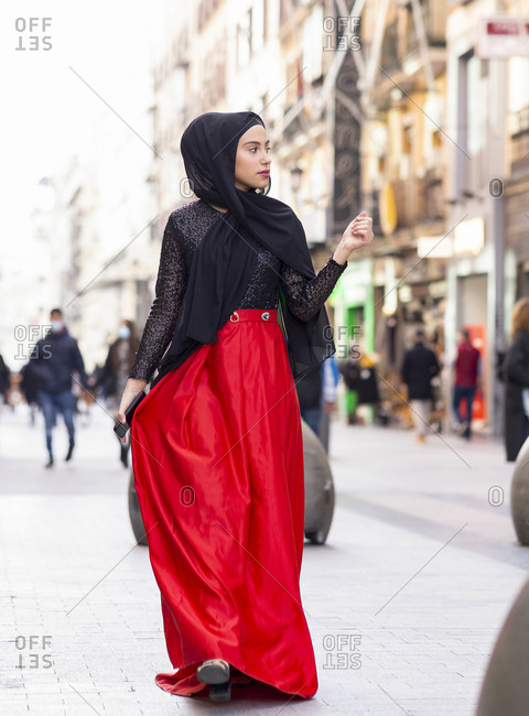Portrait of young woman wearing hijab and long skirt walking along sidewalk