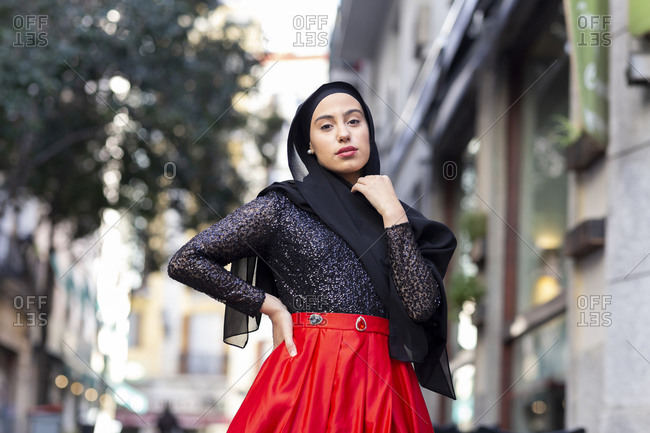 Portrait of young woman wearing black hijab posing outdoors with hand on hip