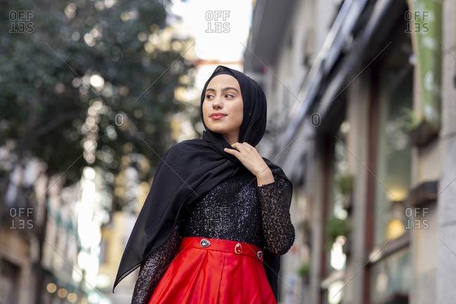 Portrait of young woman wearing black hijab standing outdoors