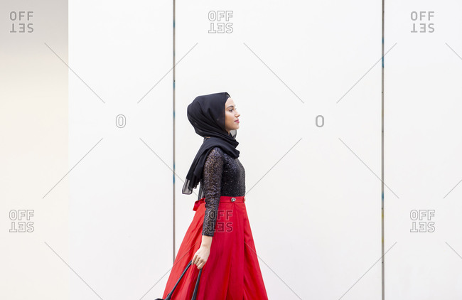 Young beautiful woman wearing hijab and long skirt walking in front of white wall with purse in hand
