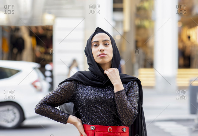 Portrait of young beautiful woman wearing black hijab posing in middle of street with hand on hip