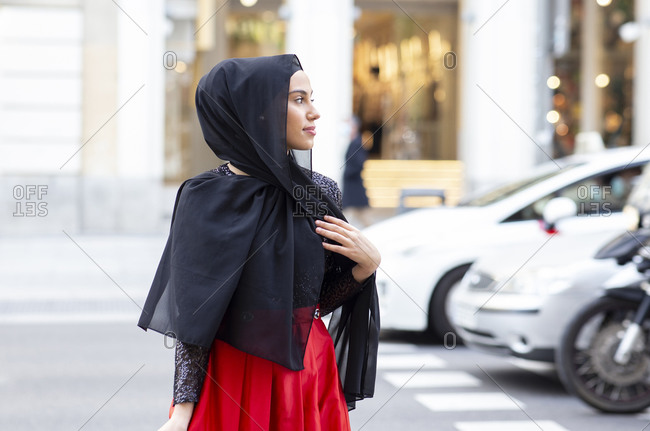 Portrait of young beautiful woman wearing black hijab posing in middle of street