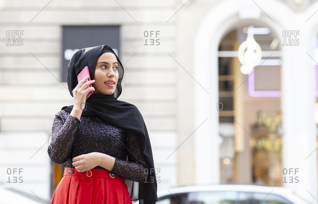 Portrait of young beautiful woman wearing black hijab talking on smart phone in middle of street