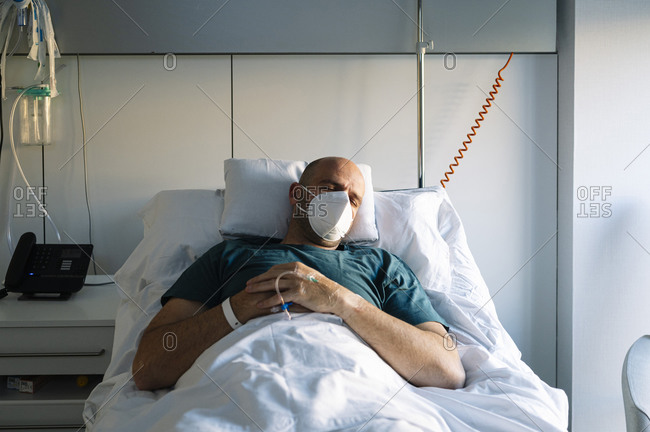 Patient wearing protective face mask sleeping on bed in hospital
