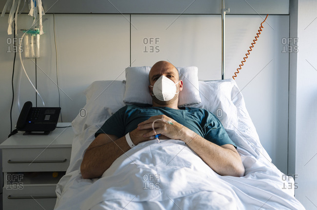 Patient with protective face mask resting on bed in hospital