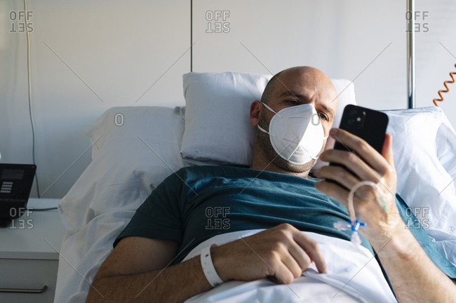 Patient using mobile phone while lying on bed in hospital