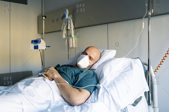 Male patient sleeping on bed in hospital