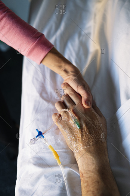 Woman holding patient hand on bed in hospital