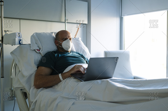 Male patient wearing face mask working on laptop while sitting on bed at hospital