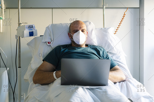 Patient wearing face mask working on laptop while sitting on bed at hospital