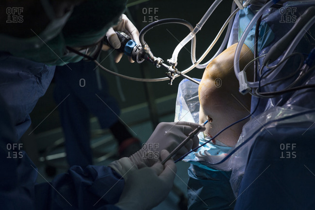 Male orthopedic surgeon performing operation on patient knee in ICU