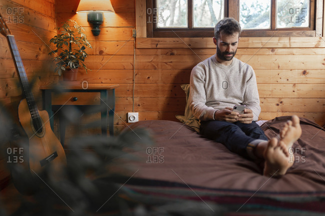 Young man using mobile phone while sitting on bed in wooden cabin