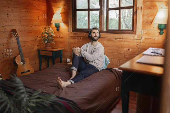 Young man with eyes closed music through headphones on bed in wooden cabin