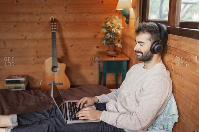 Smiling young man using laptop while listening music on bed in log cabin