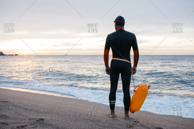 Male swimmer standing alone on sandy coastal beach with swimming float in hand