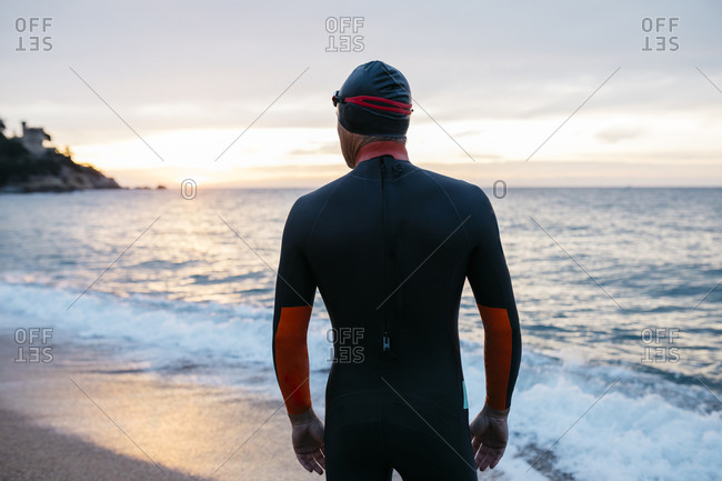 Male swimmer admiring sea at sunset