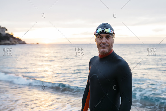 Portrait of male swimmer standing alone on coastal beach at sunset