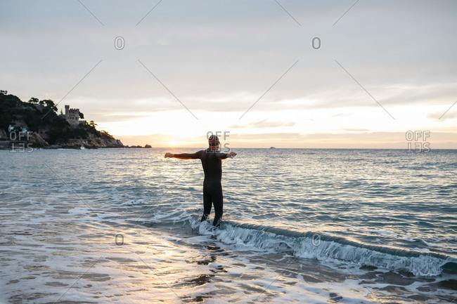 Male swimmer preparing to jump into sea water