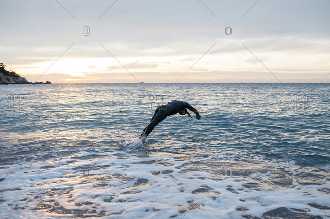 Male swimmer jumping into sea water