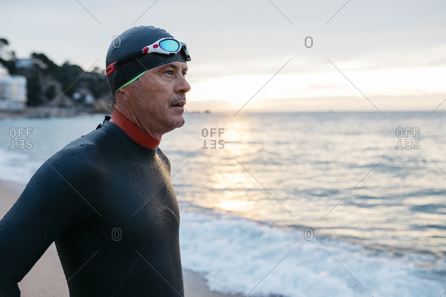 Portrait of male swimmer admiring sea at sunset