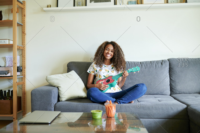 Smiling young woman with ukulele sitting on sofa in living room