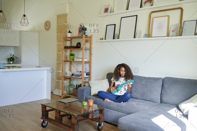 Afro young woman playing ukulele while sitting on sofa at home