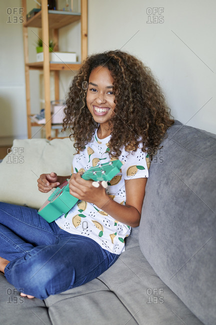 Smiling young afro woman with ukulele sitting on sofa in living room