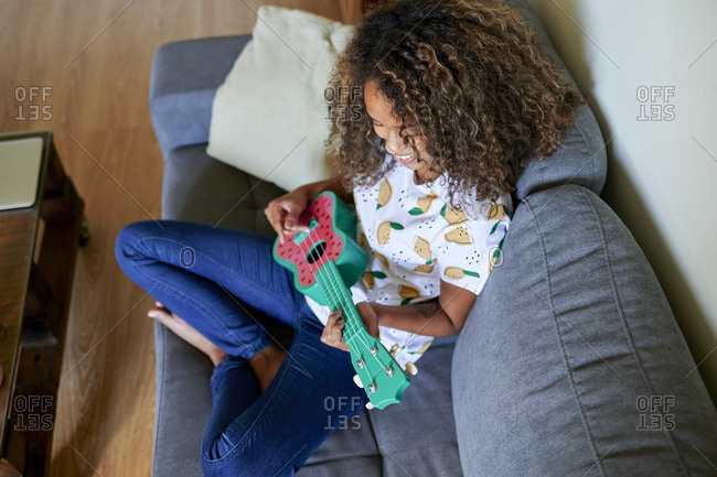 Smiling young woman with curly hair practicing to play ukulele in living room