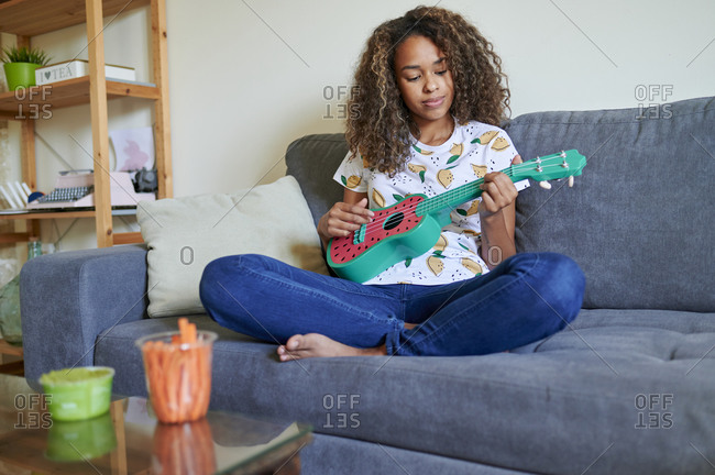 Young woman playing ukulele at home