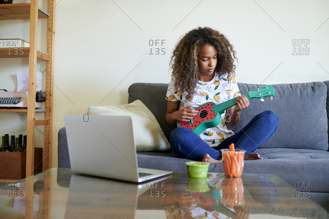 Afro young woman with laptop playing ukulele in living room