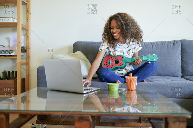 Smiling woman learning to play ukulele from laptop in living room