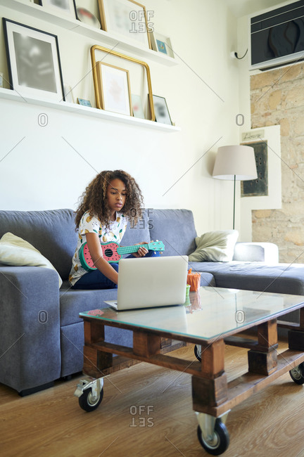 Afro young woman taking online lessons for learning ukulele at home