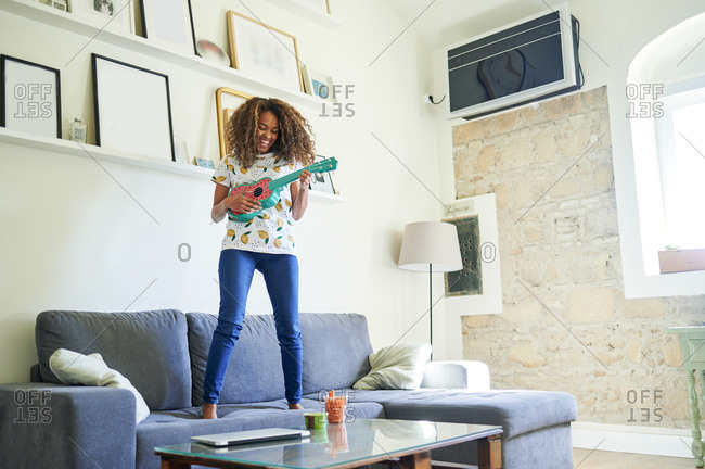 Cheerful young woman enjoying while playing ukulele at home