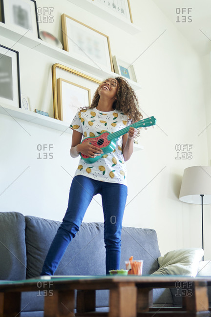Happy afro young woman with ukulele standing on sofa in living room