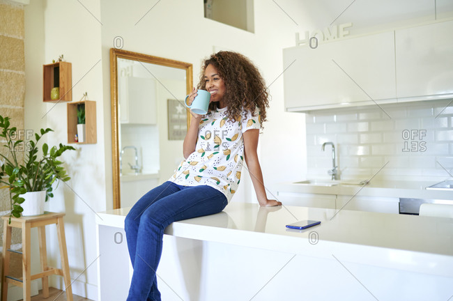 Happy afro young woman having coffee while sitting on kitchen counter at home