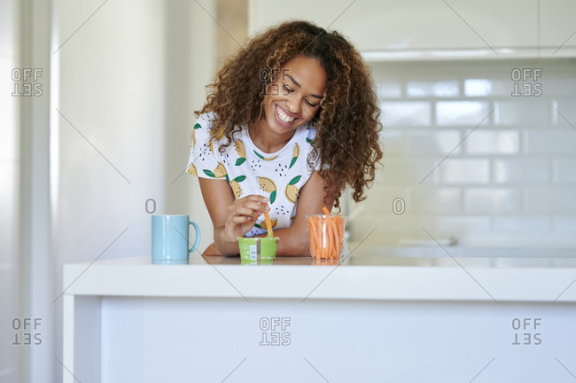 Happy young afro woman dipping carrot in guacamole sauce while leaning on counter in kitchen
