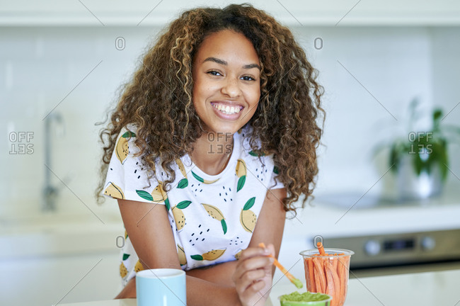 Happy woman with carrots and dipping sauce in kitchen
