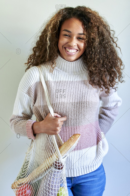 Smiling young woman with grocery shopping bag against white wall