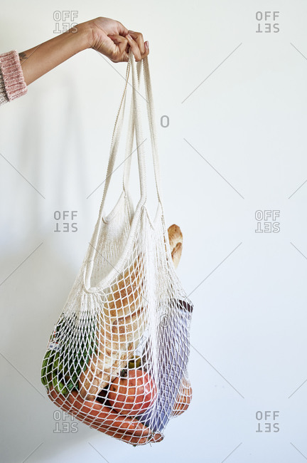 Young woman holding mesh bag with vegetables against white wall