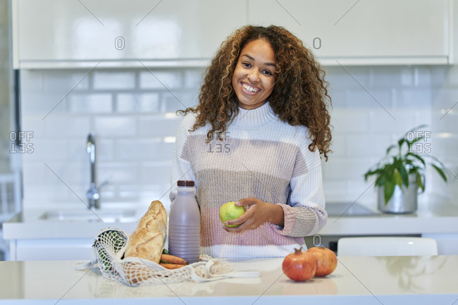 Smiling young woman holding fruit by groceries shopping bag in kitchen