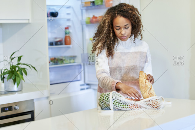 Afro young woman organizing groceries in kitchen at home