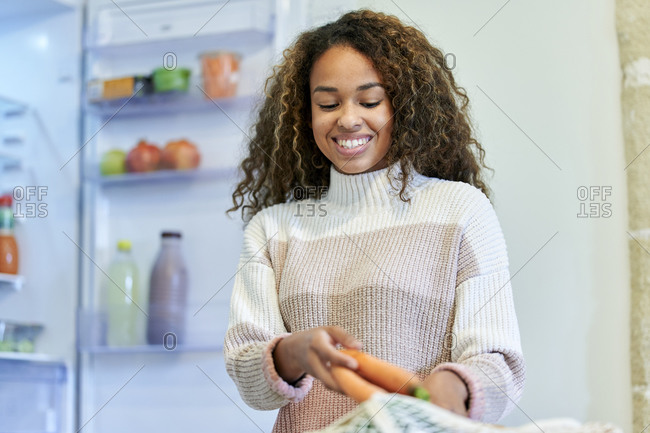 Smiling young woman taking out carrots from mesh bag in kitchen at home