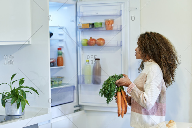 Young afro woman placing bunch of carrots in refrigerator at home