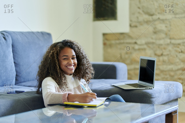 Smiling young woman with notepad at table in living room at home