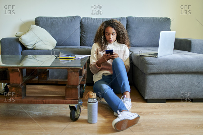 Young woman using mobile phone while sitting on floor in living room at home