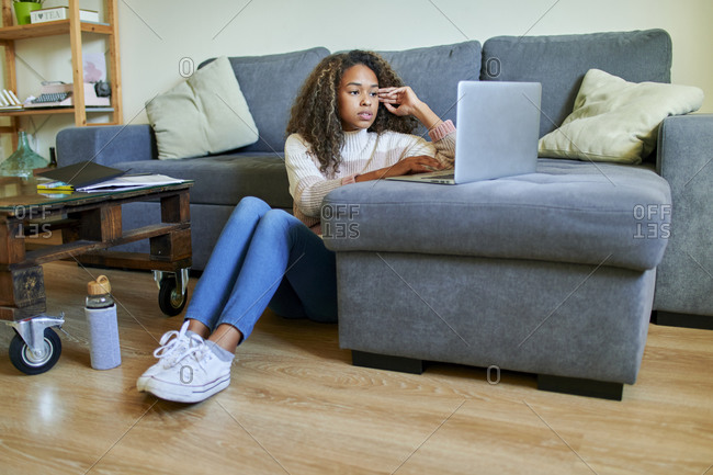 Afro young woman using laptop while sitting on floor in living room at home