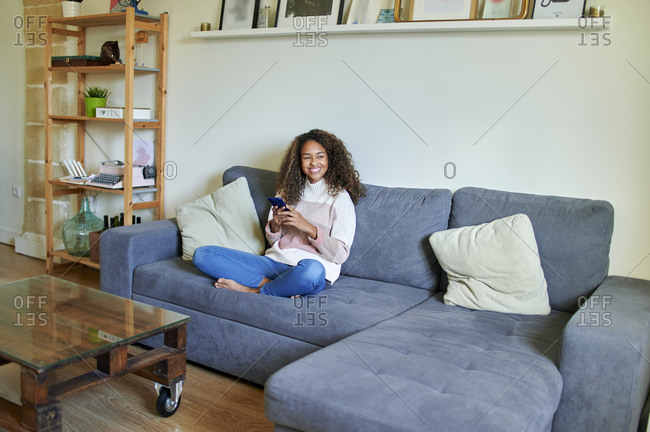 Smiling young woman contemplating while holding mobile phone at home