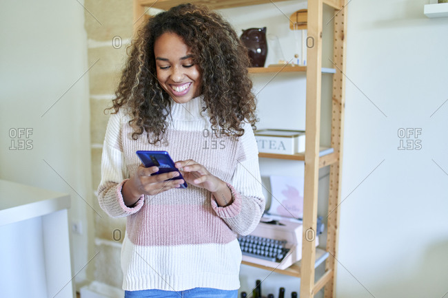 Happy young woman using smart phone against shelf at home