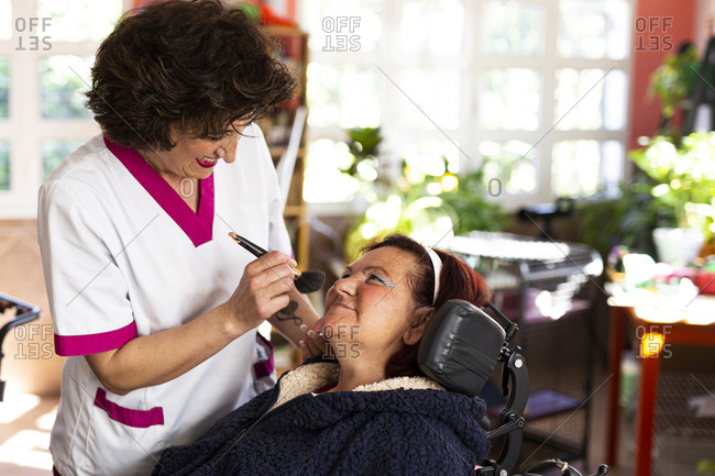 Smiling female nurse doing make-up of disabled woman in nursing home